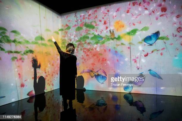 'What a Loving and Beautiful World' by teamLab is displayed as part of the 'AI More than Human' exhibition at the Barbican Curve Gallery on May 15...