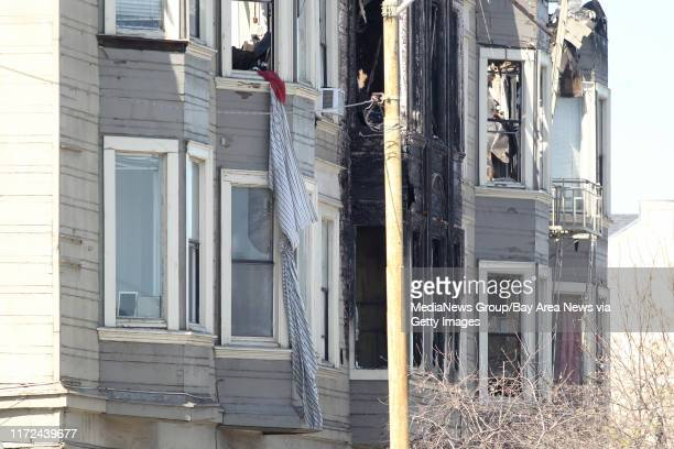 What appears to be bed sheets tied together hang from a window of a West Oakland residential building gutted by a fatal fouralarm fire in Oakland...