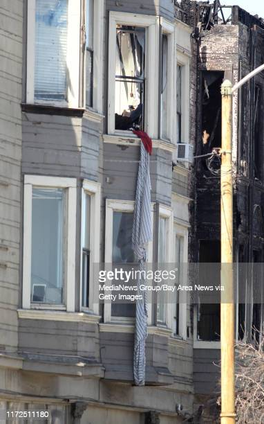 What appears to be bed sheets tied together hang from a window of a West Oakland residential building gutted by a Monday fatal fouralarm fire in...