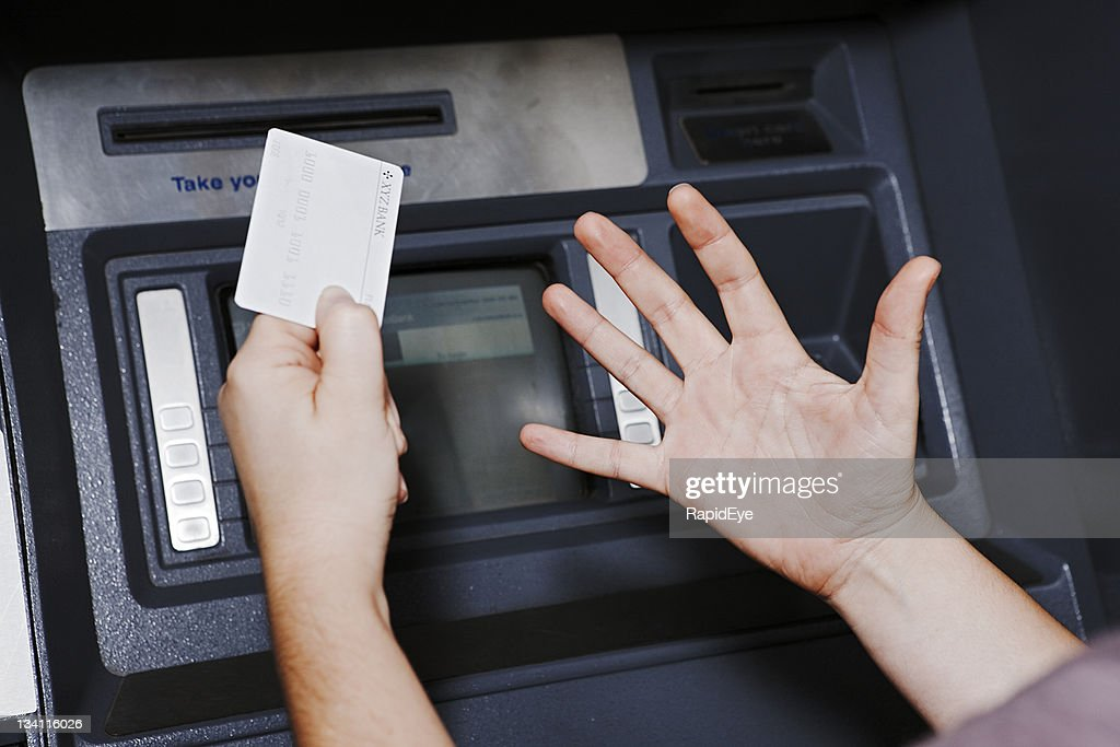 Whatever the ATM says, she isn't happy! : Stockfoto