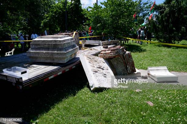 Whats left of a statue of Christopher Columbus lays party next to a city owned flatbed truck after a crew removed the statue from its base at Farnham...