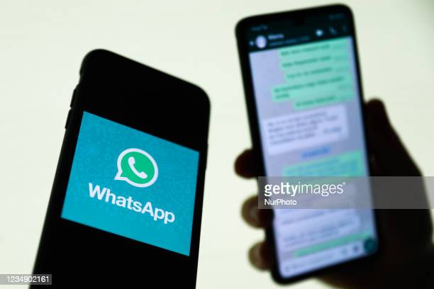 WhatsApp logo displayed on a phone screen and conversation on the WhatsApp displayed on a phone screen in the background are seen in this...