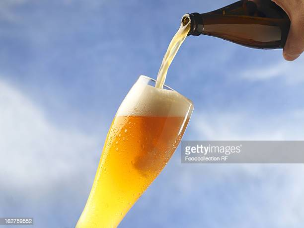 Wheat beer being poured against sky