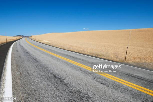 wheat field along road in countryside, tensed, idaho, united states - next to stock pictures, royalty-free photos & images