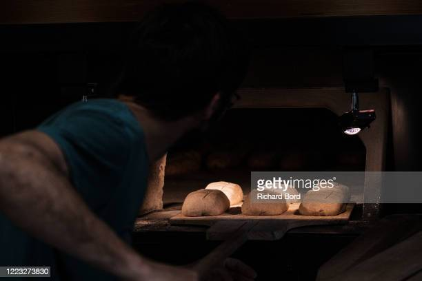 Wheat producer miller and baker Fabien Abry bakes breads in the wood oven at 'Le Fournil des Paysans' on May 06 2020 in Mesigny France Due to the...