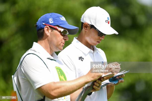 Whee Kim of Korea speaks with his caddie on the 16th tee during the first round of the John Deere Classic at TPC Deere Run on July 12 2018 in Silvis...