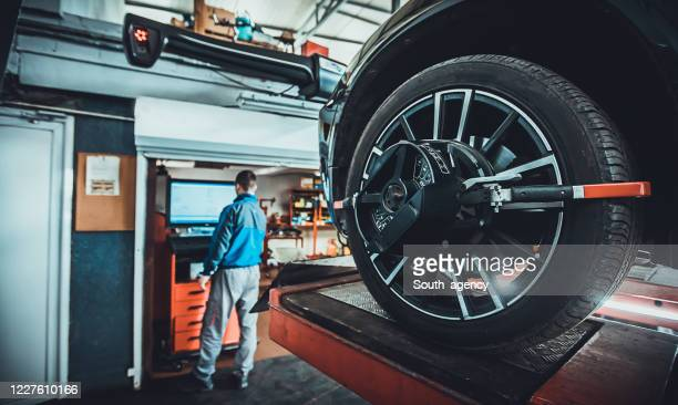 wheel alignment equipment on a car wheel in a repair station - wheel stock pictures, royalty-free photos & images