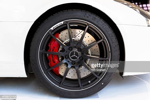 Wheel and ventilated disc brakes of AMG Mercedes SLS 63 showing red caliper at AMG showroom in Munich Bavaria Germany