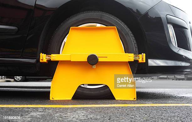 A wheel clamp attached to the wheel of a black car
