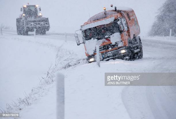 A wheel loader approaches a truck that has slipped off the track due to heavy snowfall on January 18 2018 near Bruesewitz northeastern Germany...