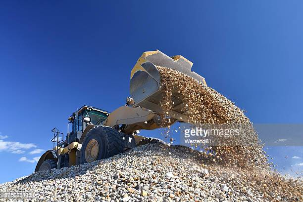 wheel loader loading stones in gravel pit - gravel stock pictures, royalty-free photos & images