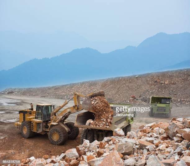 Wheel loader machine unloading rocks in the open-mine of iron ore,Pingshuo mining site,China