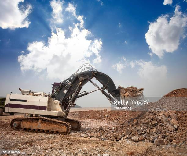 Wheel loader machine unloading rocks in the open-mine of iron ore,China