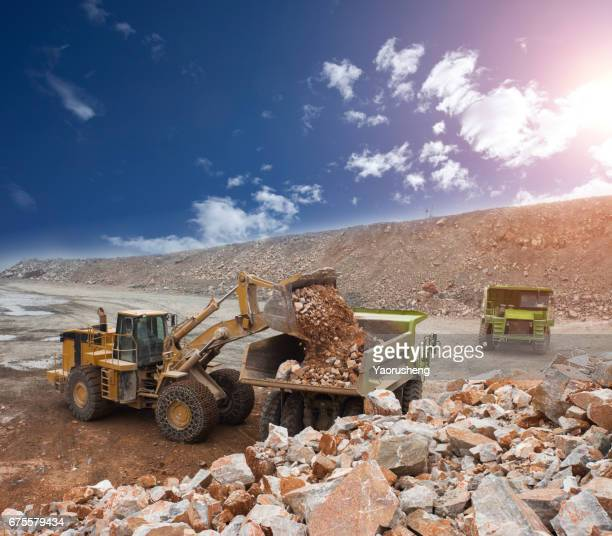 wheel loader machine unloading rocks in the open-mine of iron ore,china - gold mining stock photos and pictures