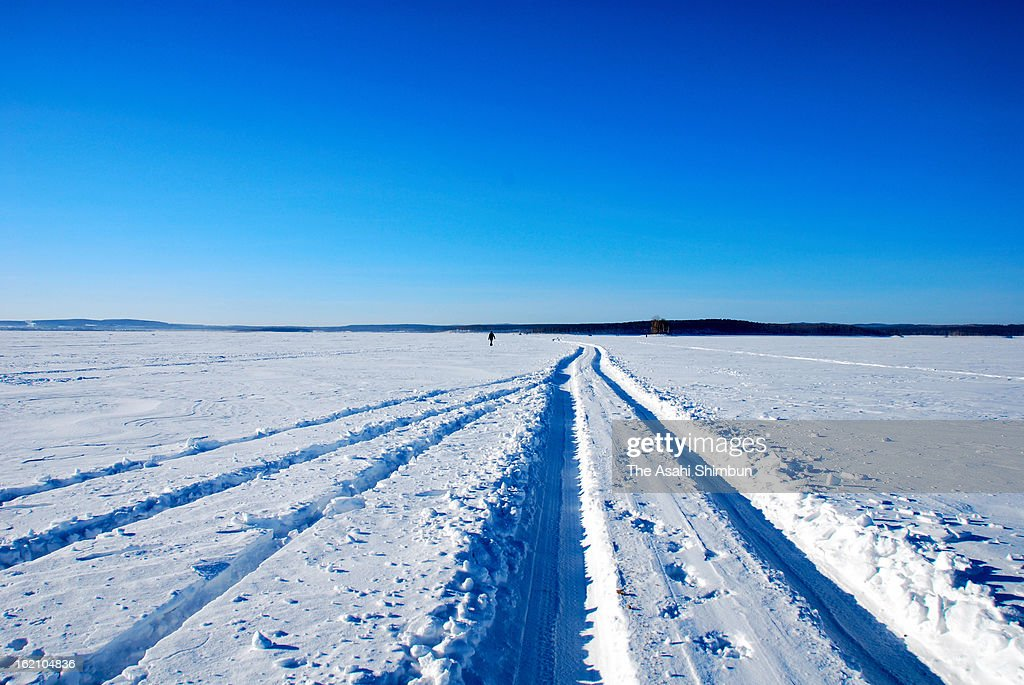 Wheel tracks lead to a hole in the ice of Chebarkul Lake on March 16, 2013 some 80 kilometers from Chelyabinsk, Russia. Local government reported more than 1,100 people injured, mostly by flying glass broken by the shock wave of the meteor explosion.