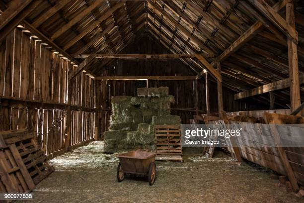 wheelbarrow and stack of hay bale in wooden barn - barn stock pictures, royalty-free photos & images