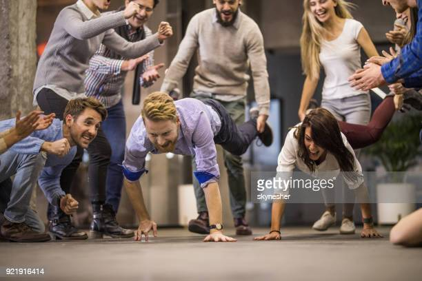 wheelbarrow race on a break in the office! - acrobatic activity stock photos and pictures