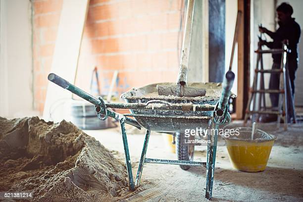 Wheelbarrow with cement in repairing apartment