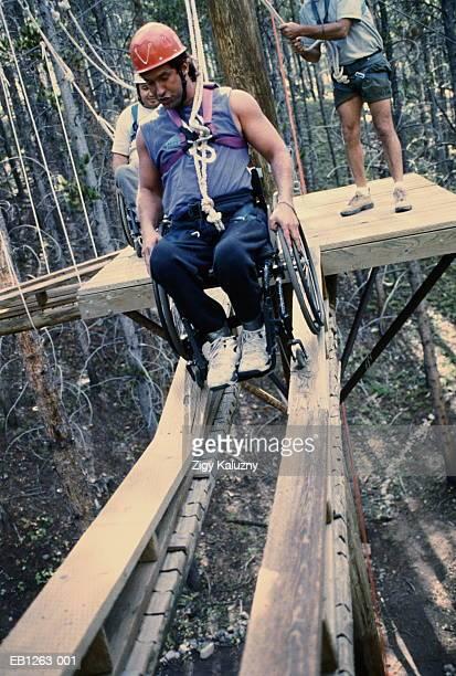 wheelchair athlete maneuvering high ropes course - schrägansicht stock-fotos und bilder