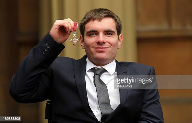 Wheelchair Athlete Michael Bushell holds his medal after being made a Member of the Order of the British Empire by the Prince of Wales during an...