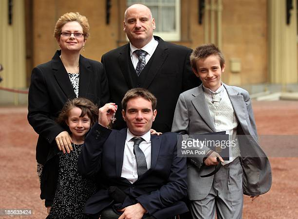 Wheelchair Athlete Michael Bushell poses with family members as he holds his medal after being made a Member of the Order of the British Empire by...