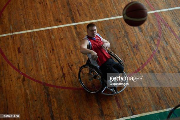 wheelchair athlete throwing ball into basket - cliqueimages stock pictures, royalty-free photos & images