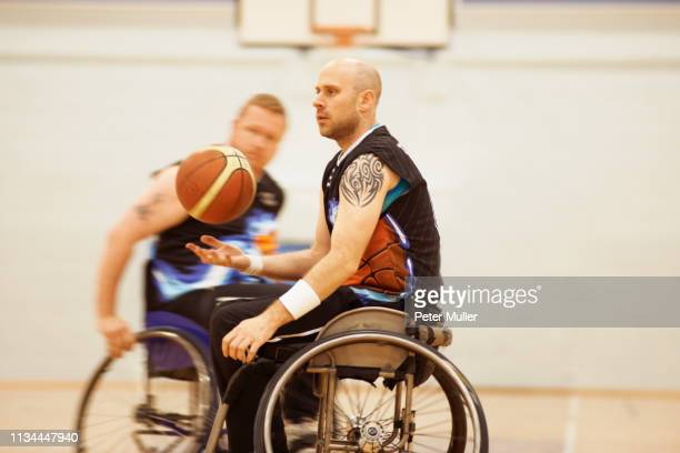 wheelchair basketball player bouncing ball - sports equipment stock pictures, royalty-free photos & images