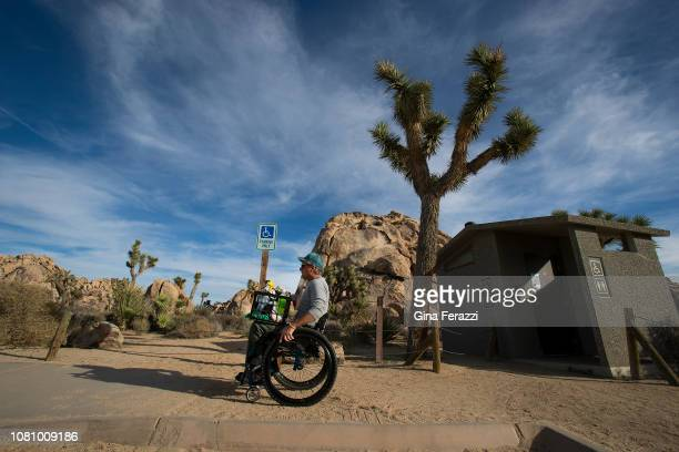 Wheelchair bound Rand Abbott of Joshua Tree carries carries cleaning supplies on his lap after cleaning a bathroom stall in Joshua Tree National Park...