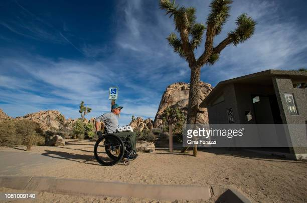 Wheelchair bound Rand Abbott of Joshua Tree carries extra toilet paper to refill a bathroom stall after cleaning it in Joshua Tree National Park on...
