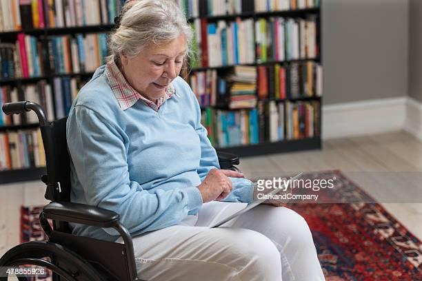Wheelchair Bound Senior Woman Using a Digital Tablet