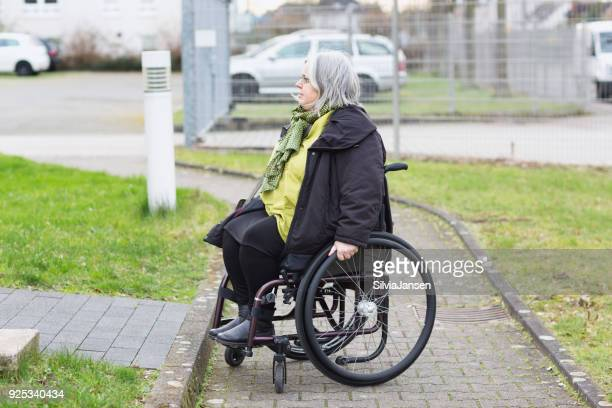 wheelchair driver facing a barrier - imbalance stock photos and pictures
