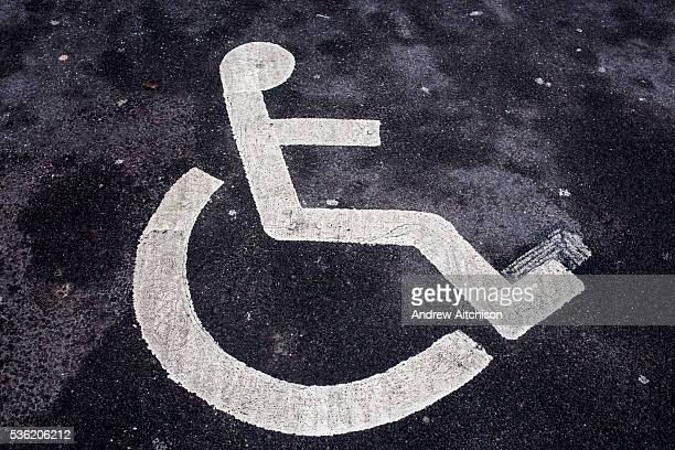 Wheelchair figure stenciled in white lines on tarmac as a sign for a disabled parking bay Middlesborough England UK