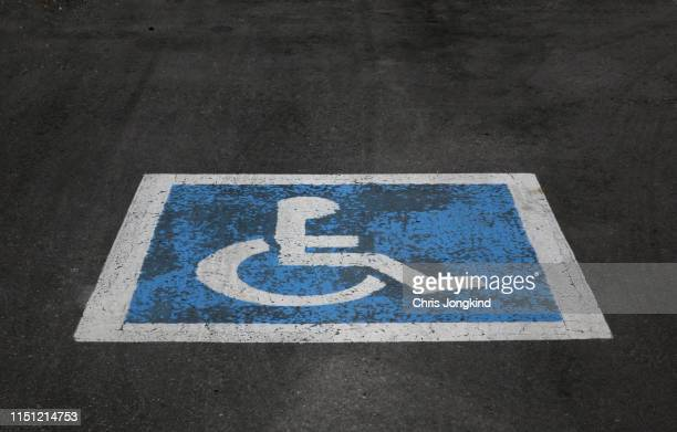 wheelchair marking in disabled parking space - disabled sign stock photos and pictures