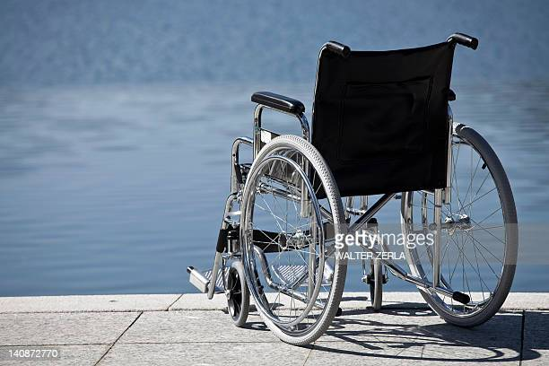 wheelchair parked by water - paraplegic stock photos and pictures