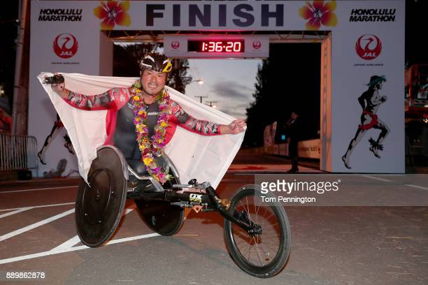 Wheelchair participant Masazumi Soejima poses with a flag flag after crossing the finish line to win the Men's Wheelchair division during the...