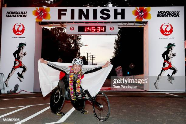 Wheelchair participant Wakako Tsuchida poses with a flag after crossing the finish line to win the Women's Wheelchair division during the Honolulu...