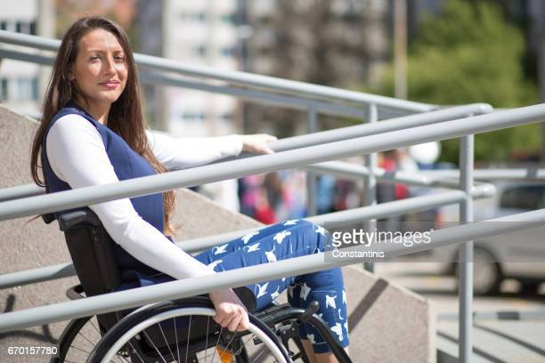 wheelchair ramp help for a young woman - paraplegic stock photos and pictures