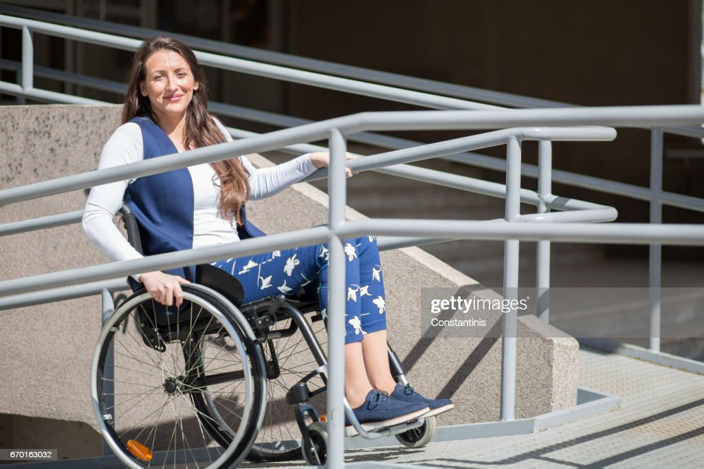 wheelchair ramp help for a young woman : Stock Photo