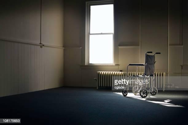 Wheelchair Sitting in Empty Room By Window
