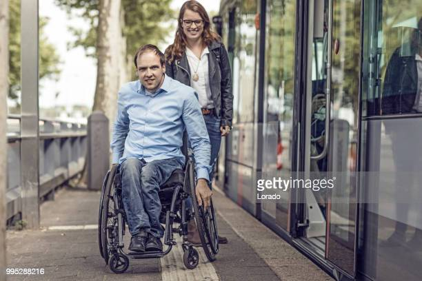wheelchair using young man and his girlfriend travelling around a modern city - assistive technology stock photos and pictures