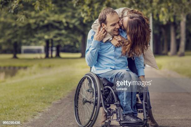 Wheelchair using young man and his girlfriend walking together through a city park