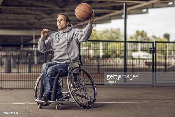 cadeira de rodas usando o jovem durante uma sessão de treino de basquete urbano ao ar livre - cadeira de rodas elétrica - fotografias e filmes do acervo