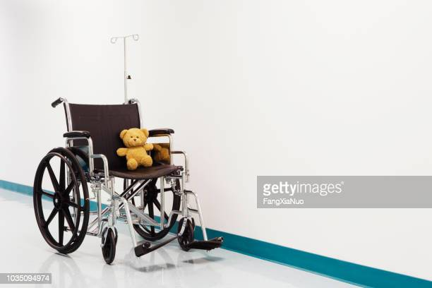 wheelchair with teddy bear in hospital corridor - gift shop stock pictures, royalty-free photos & images