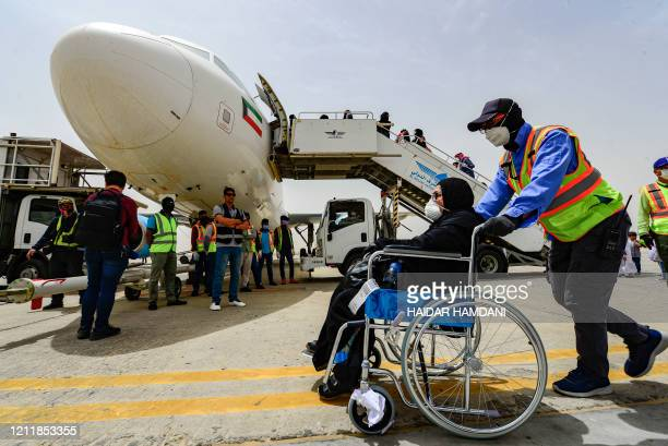 Wheelchair-bound woman is assisted to board a Jazeera Airways Airbus A320-214 aircraft carrying Kuwaitis stranded in Iraq due to the COVID-19...