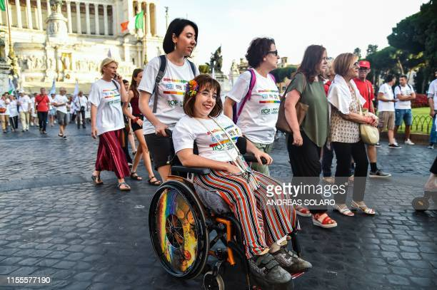 A wheelchairbound woman smiles as she takes part in a 'Disability Pride Parade' by people from Italian disability organisations in front of the...