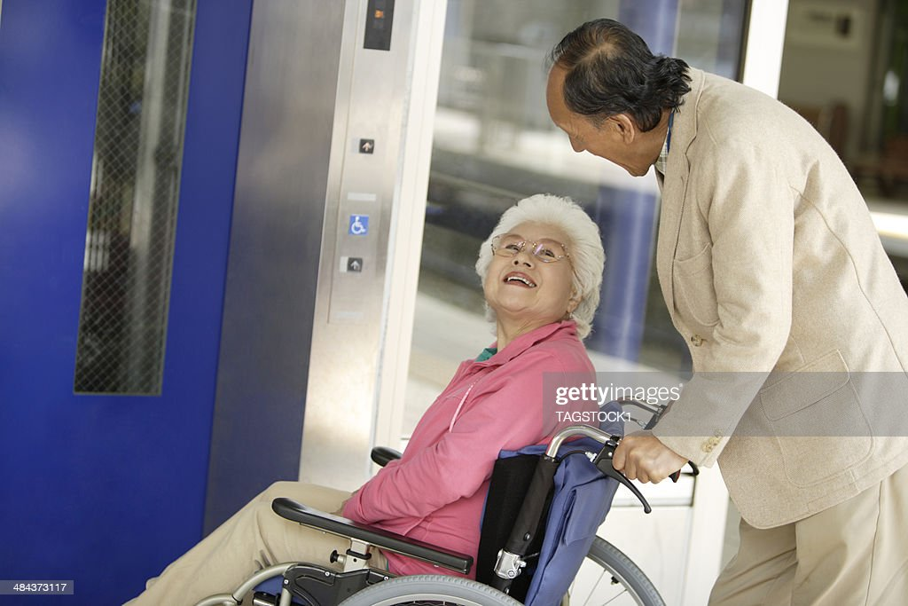 Wheelchaired wife and husband using an elevator : Stock Photo