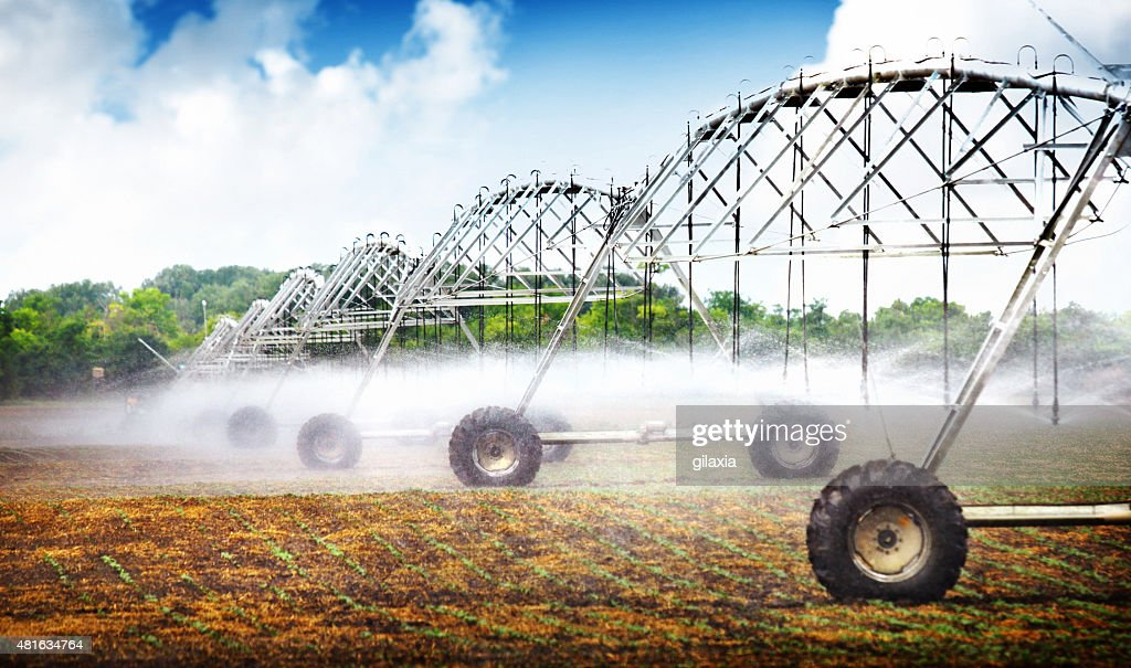Wheeled irrigation on agricultural soil. : Stock Photo