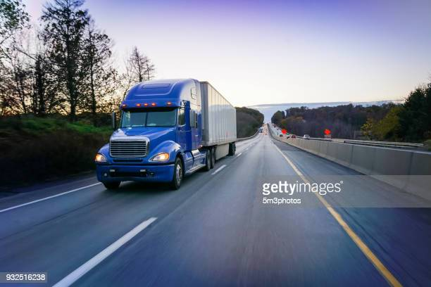 18 wheeler blue semi truck on highway at dusk - driverless transport stock pictures, royalty-free photos & images