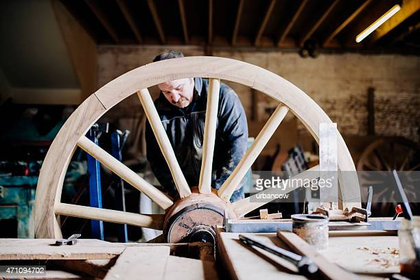 Wheelwright standing in his workshop working on a wooden cartwheel