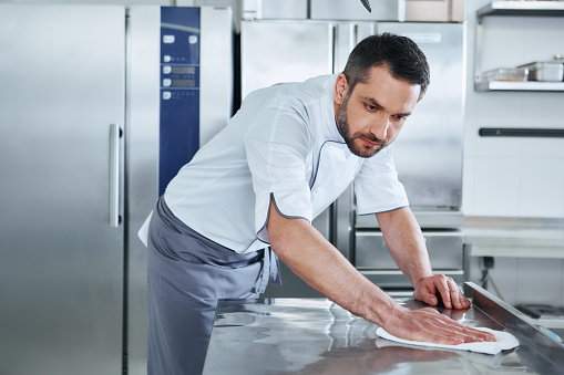 When preparing foods keep it clean, a dirty area should not be seen. Young male professional cook cleaning in commercial kitchen 1142169890